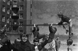 Kuvassa poikia kiipeilemässä telineellä ja poseeraamassa Kallion kansakoulun pihalla Neljännellä linjalla. Simo Rista/Helsingin kaupunginmuseo.