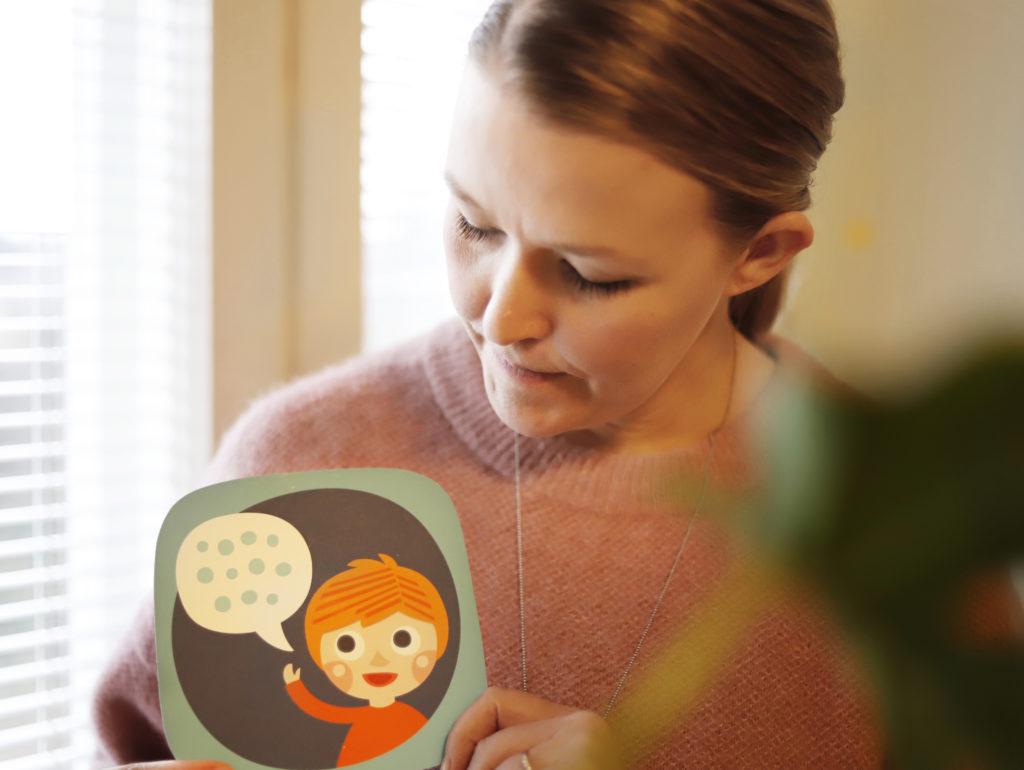 Nainen näyttää puhumista kuvaavaa kommunikaatiokorttia