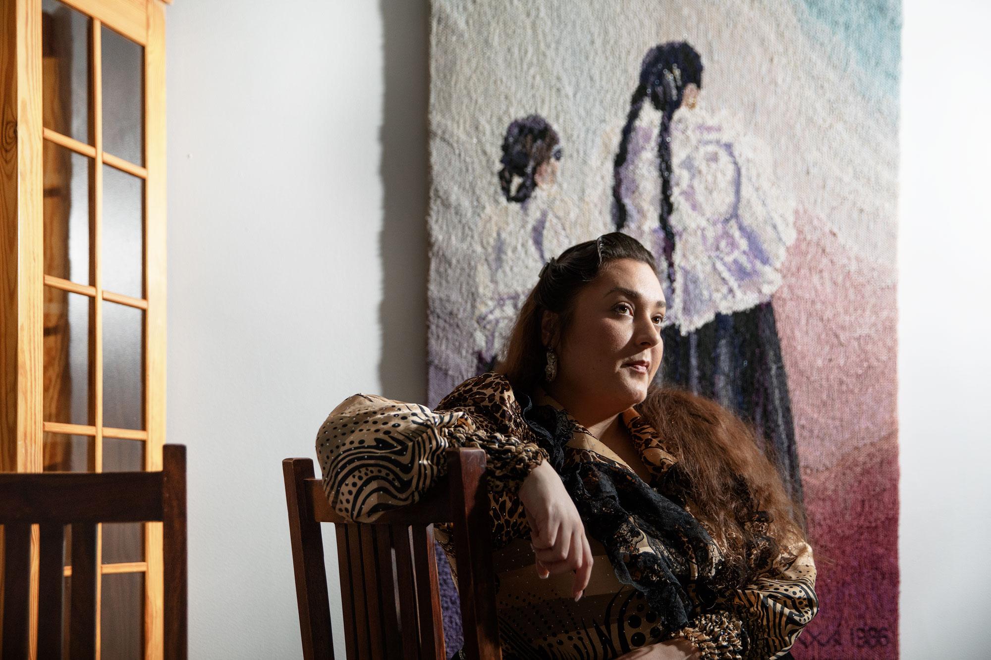 Puolikuva naisesta istumassa tuolilla. Taustalla värikäs ryiijy