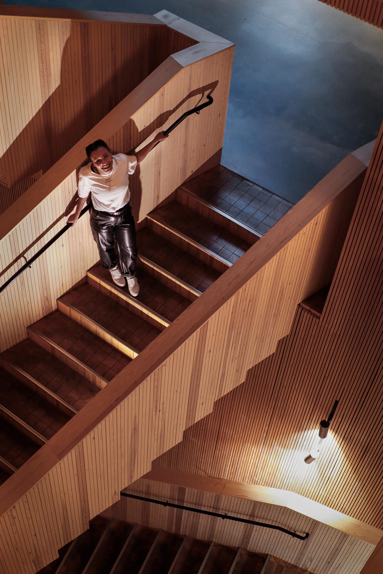 Henkilö seisoo sisätiloissa portaikossa ja nojaa kaiteeseen, yleiskuva