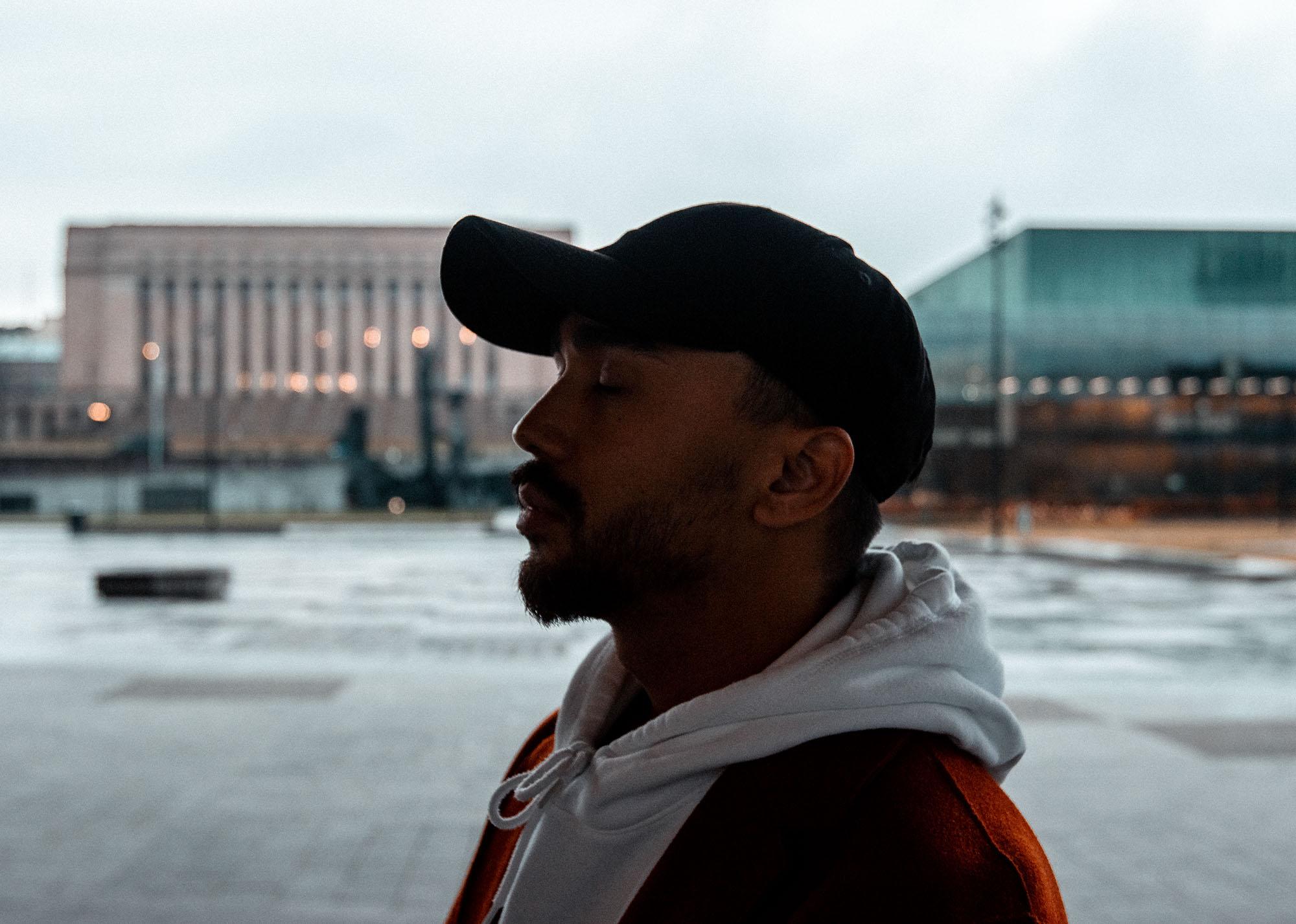 Lippalakkipäisen nuoren miehen siluetti, taustalla aukio.