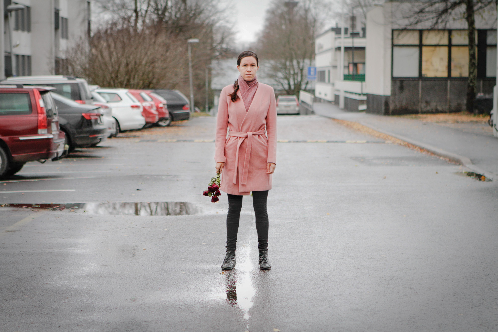 Punaiseen takkiin pukeutunut nainen seisoo kadulla ruusukimppu kädessään.