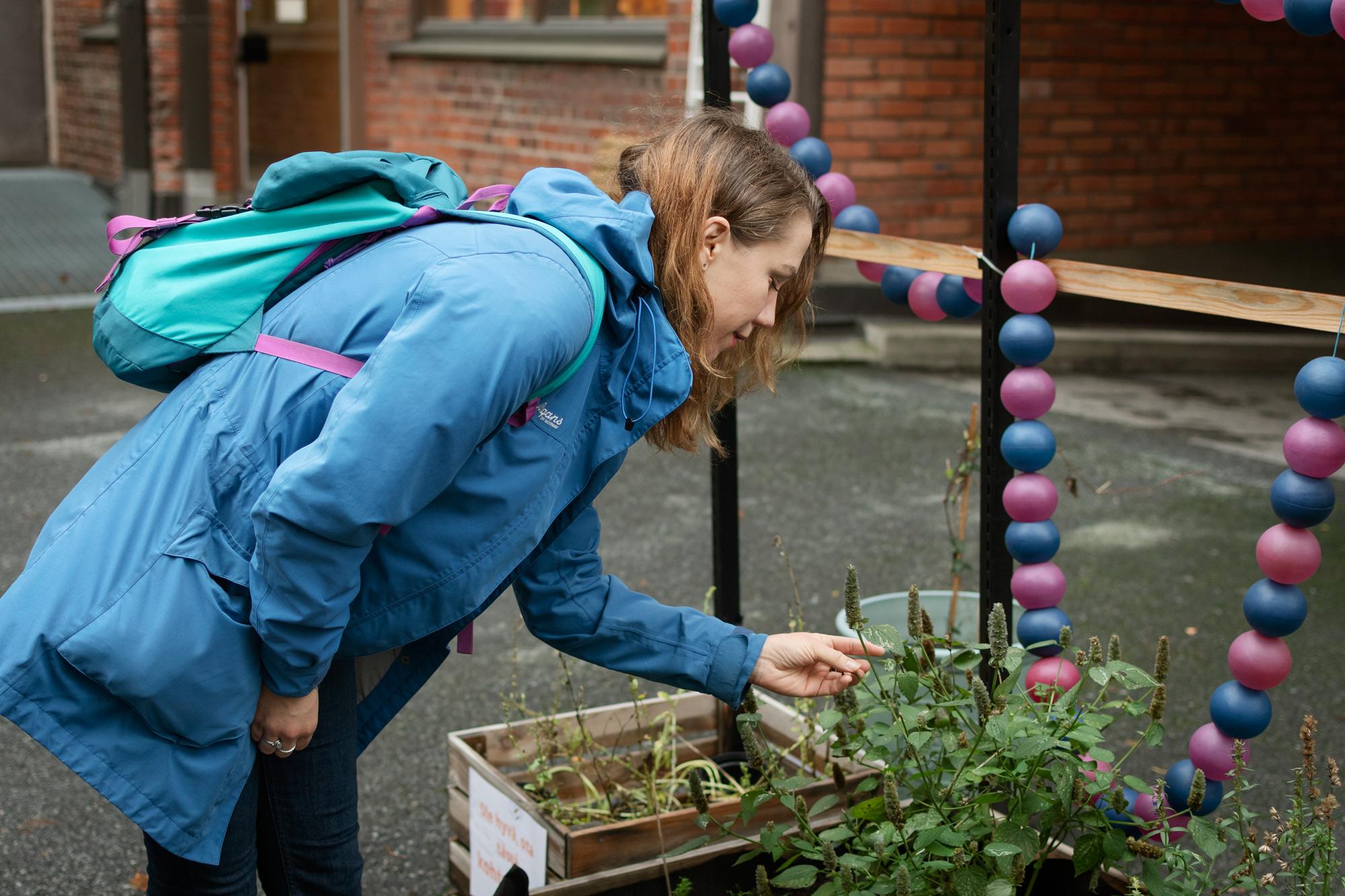 Nainen kumartuu katsomaan kasvia ulkona