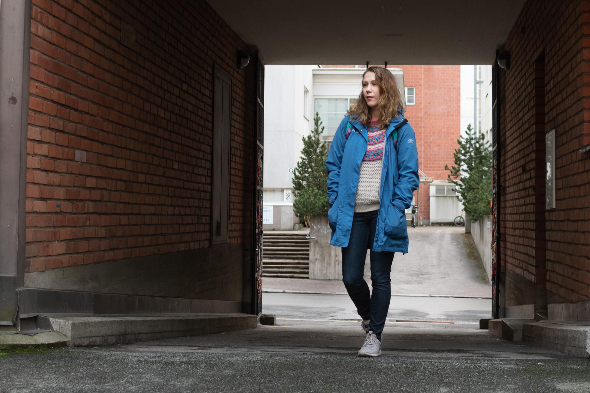 Henkilö kävelee porttikongista rakennuksen sisäpihalle