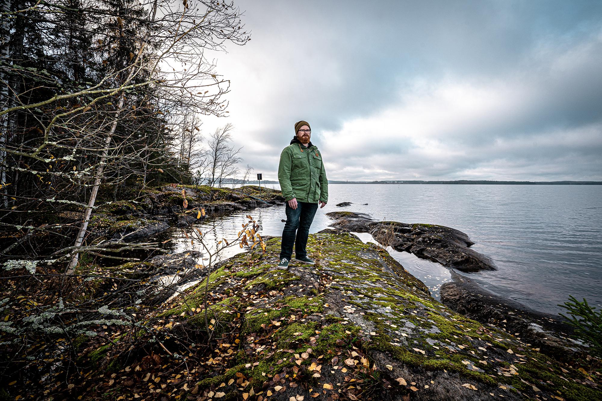 Mieshenkilö seisoo kivikon päällä järven rannassa.