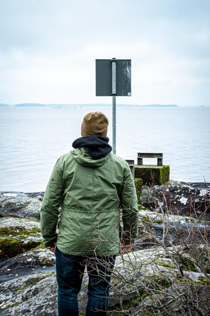 Mies vihreässä takissa kuvattuna selkäpuolelta rannalta.
