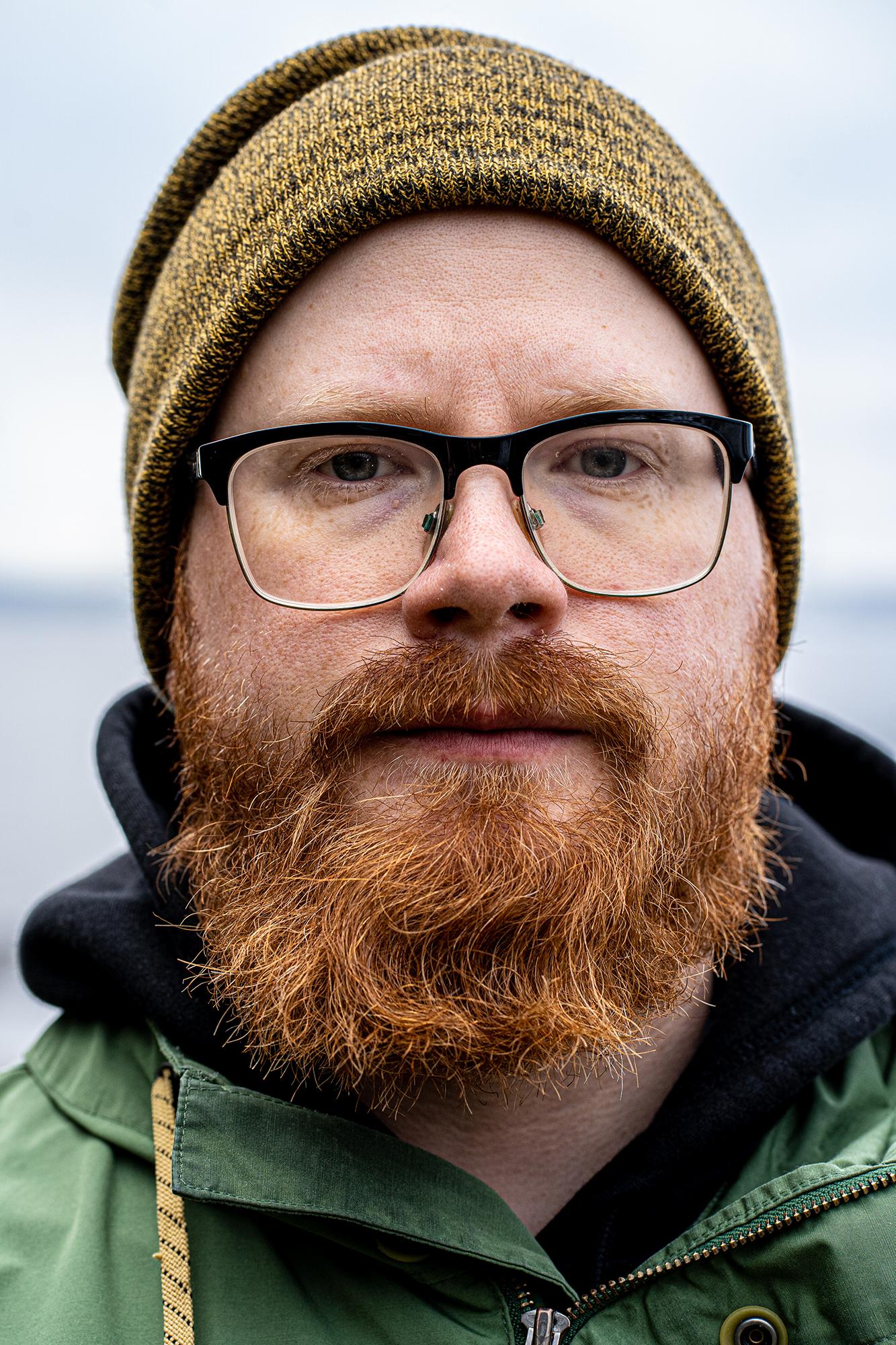 Lähikuva silmälasipäisen, pipopäisen parrakkaan henkilön kasvoista