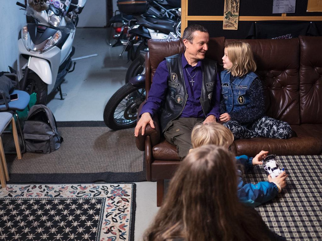 Sohvalla istuu aikuinen ja lapsi. Etualla näkyy toinen aikuinen ja pienempi lapsi, jotka istuvat pöydän ääressä. Lapsella on kädessään lelumoottoripyrä. Taustalla näkyy moottoripyöriä.