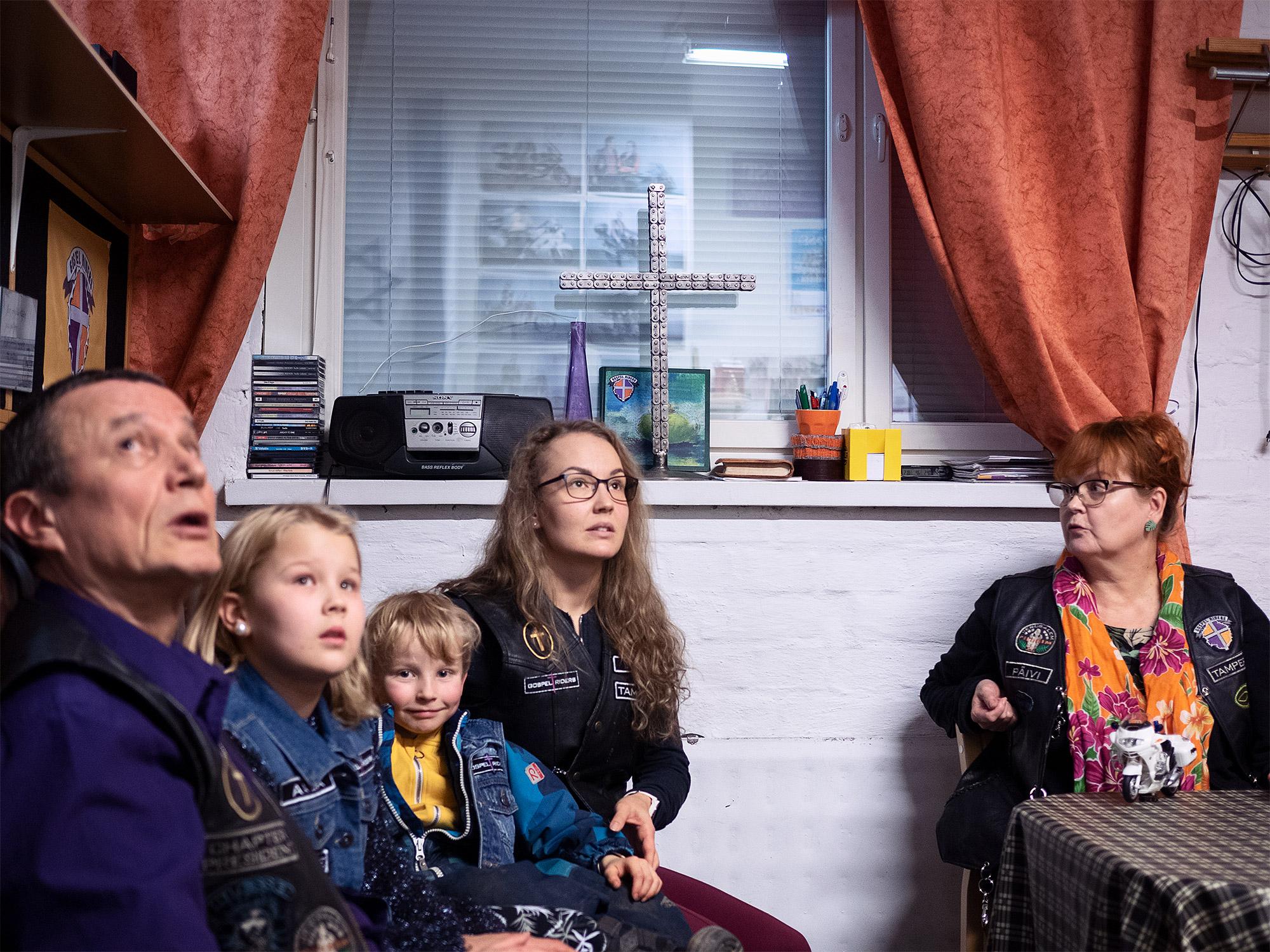 Kuvassa on kolme aikuista ja kaksi lasta. Kaksi aikuisista ja toinen lapsi katselee yläviistoon, pienempi lapsi katsoo suoraan kameraan. Kolmas aikuinen istuu hieman erillään muista pöydän ääressä, ja katsoo muuta porukkaa. Heillä kaikilla on nahkaiset kerholiivit päällä. Henkilöiden takana näkyy ikkunalauta, jossa on metallista valmistettu risti ja muita tavaroita kuten radio ja kasa cd-levyjä.