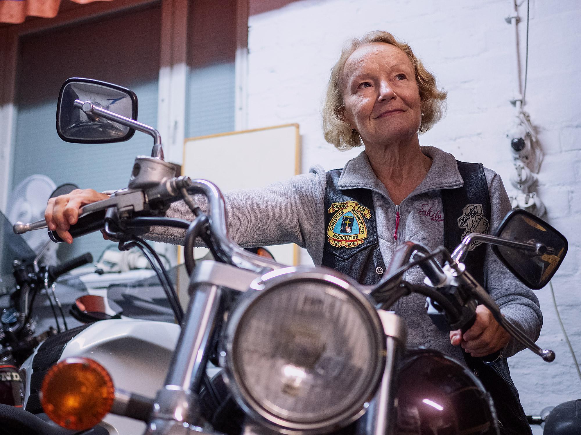 Kuvassa on henkilö sisätiloissa moottoripyörän päällä. Henkilö pitää pyörän kahvoista kiinni ja katselee yläoikealle. Hänellä on päällään harmaa pusakka ja yllään nahkaiset kerholiivit, jossa on kangasmerkkejä. Kangasmerkeissä on muun muassa ristin kuvia.