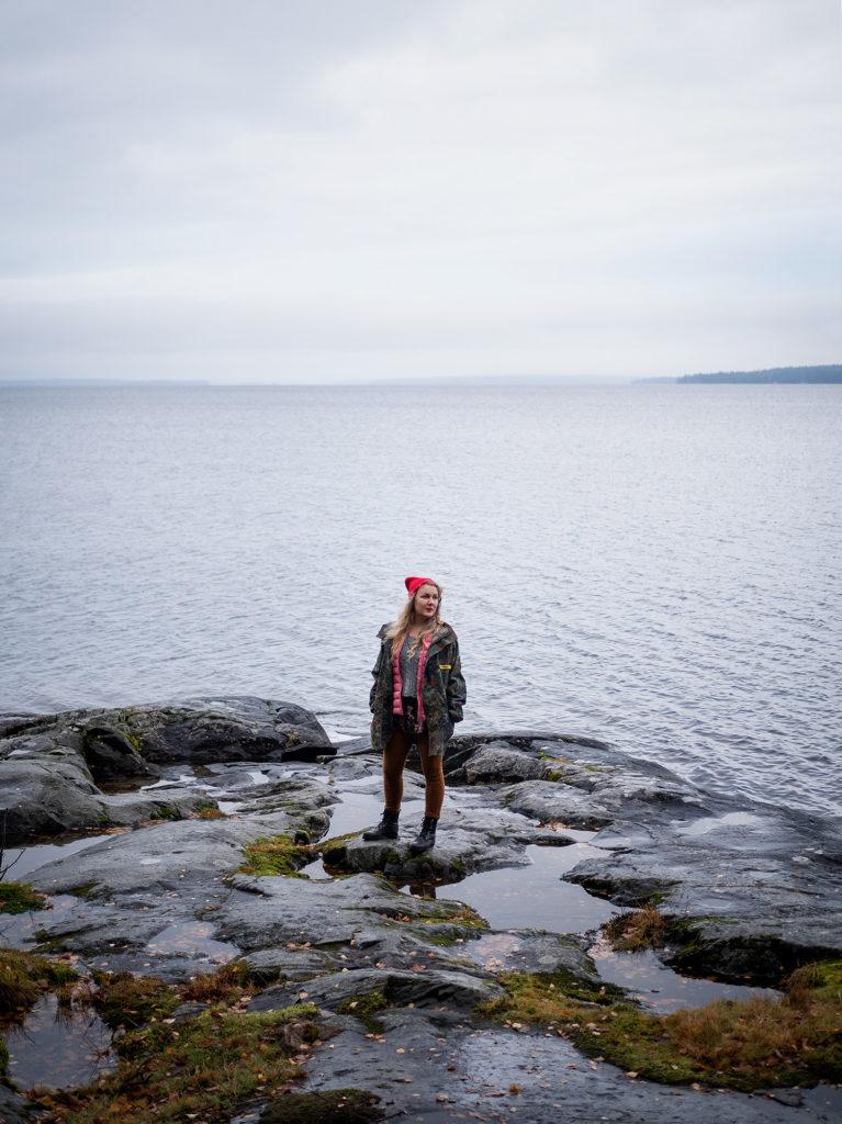 Henkilö on kuvattu kaukaa. Hän seisoo rantakalliolla. Takana avautuu järvenselkä ja pilvinen taivas.