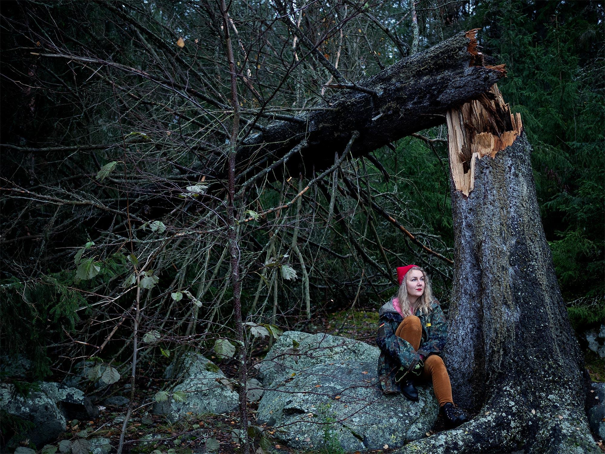 Kuvassa ollaan metsässä. Henkilö istuu suuren kaatuneen puun vieressä. Puu on katkennut keskeltä runkoa, ja kaatunut osa nojaa vielä ystyssä olevaan. On hieman hämärää.