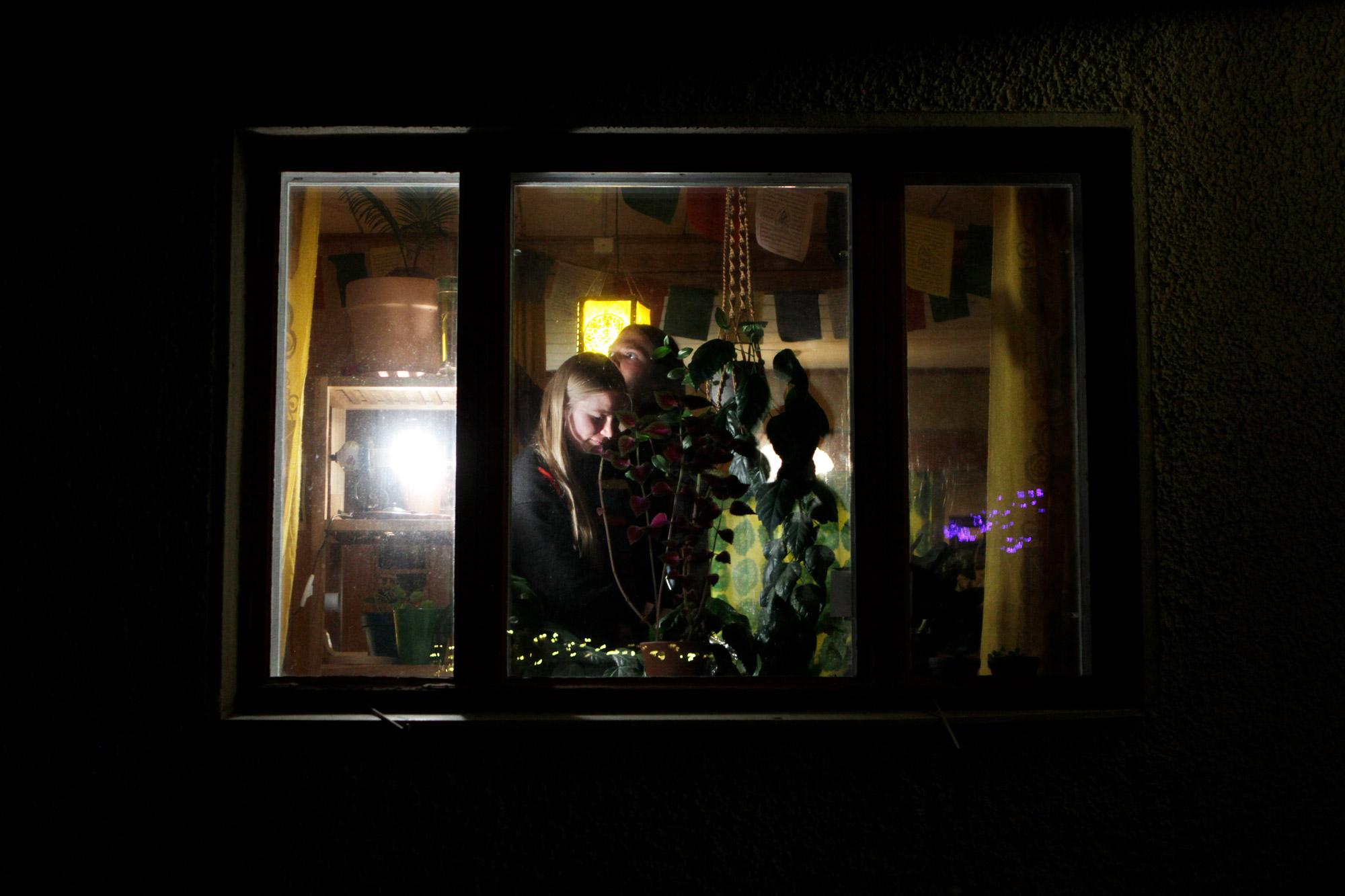 Nainen ja mies kastelevat kukkia ikkunan ääressä illalla.