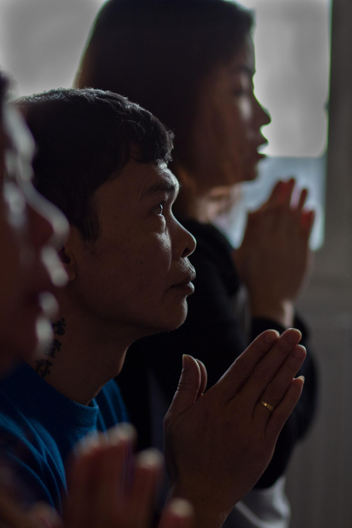 Henkilö rukoilee kämmenet vastakkain, puolilähikuva