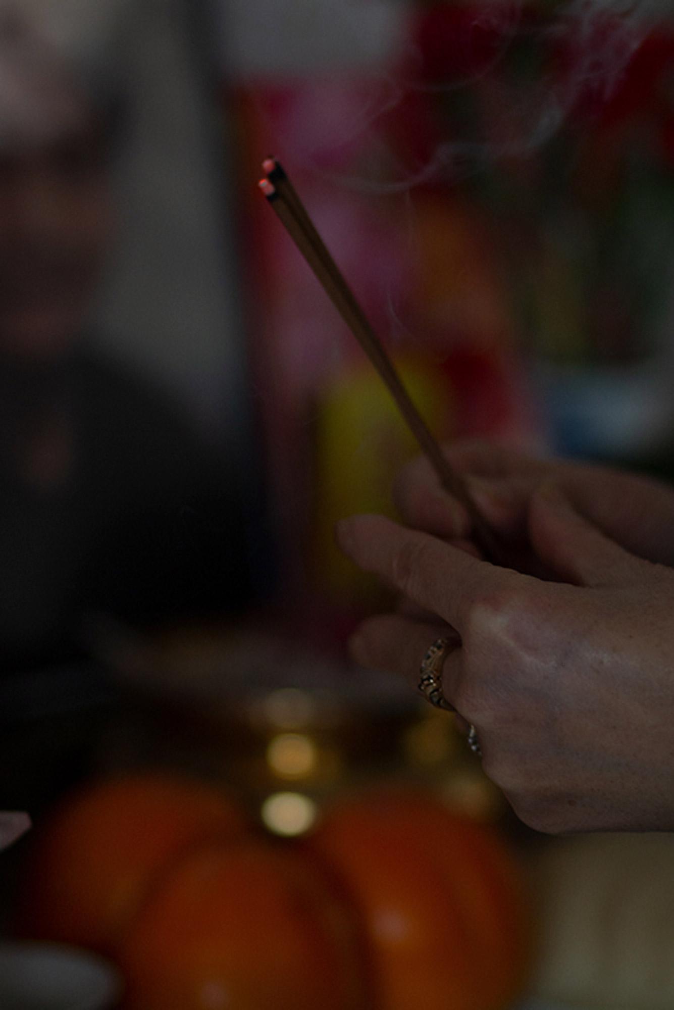 Henkilö pitää palavia suitsukkeita käsissään