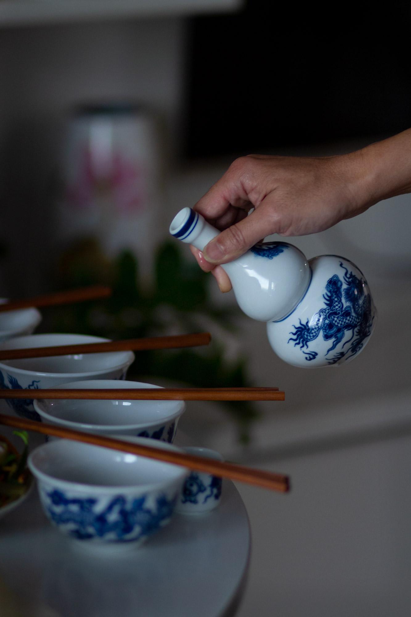 Henkilön kädessä keraaminen kaadin, pöydälle katettuna astioita