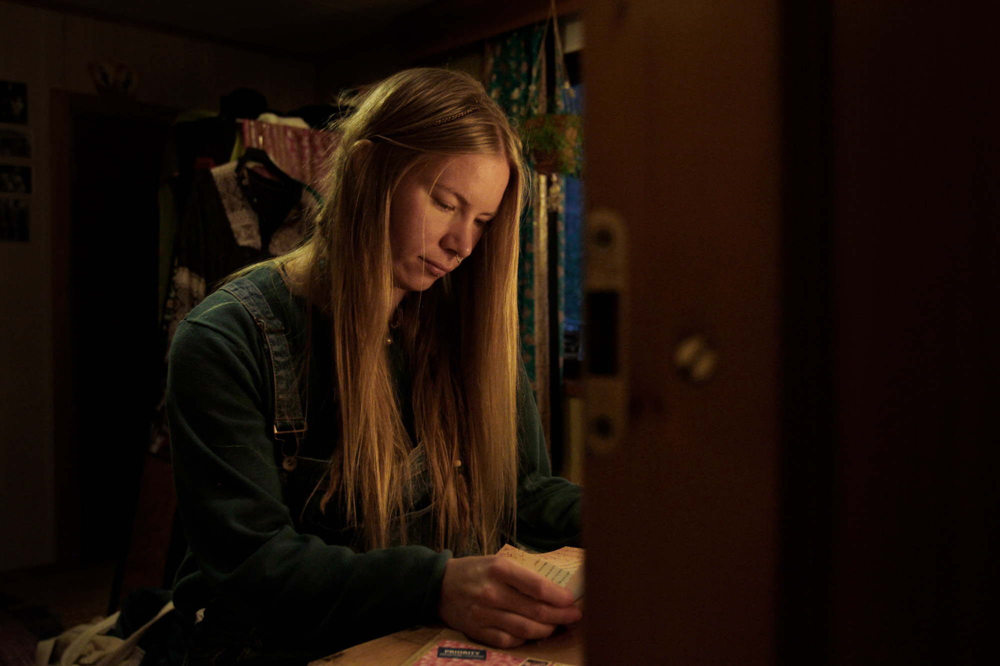 pitkähiuksinen nainen lukee kirjettä huoneessa lampun valossa