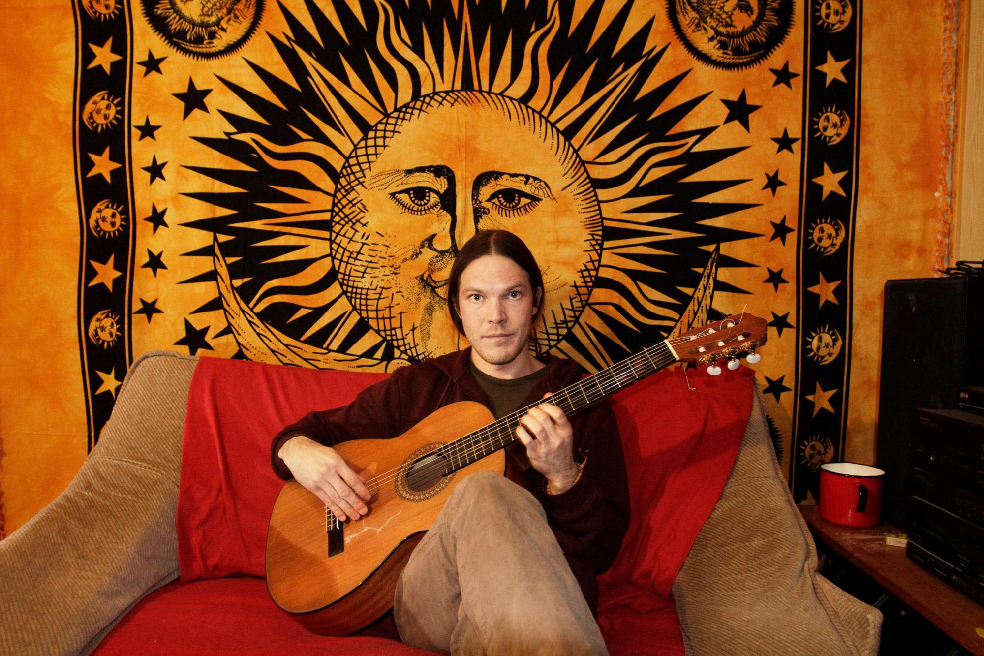 Mies istuu sohvalla ja soittaa kitaraa.