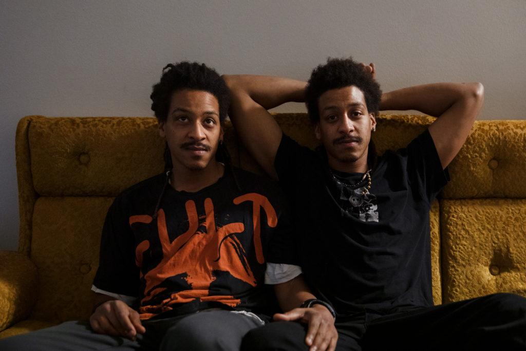 Kaksi miestä istuu sohvalla.