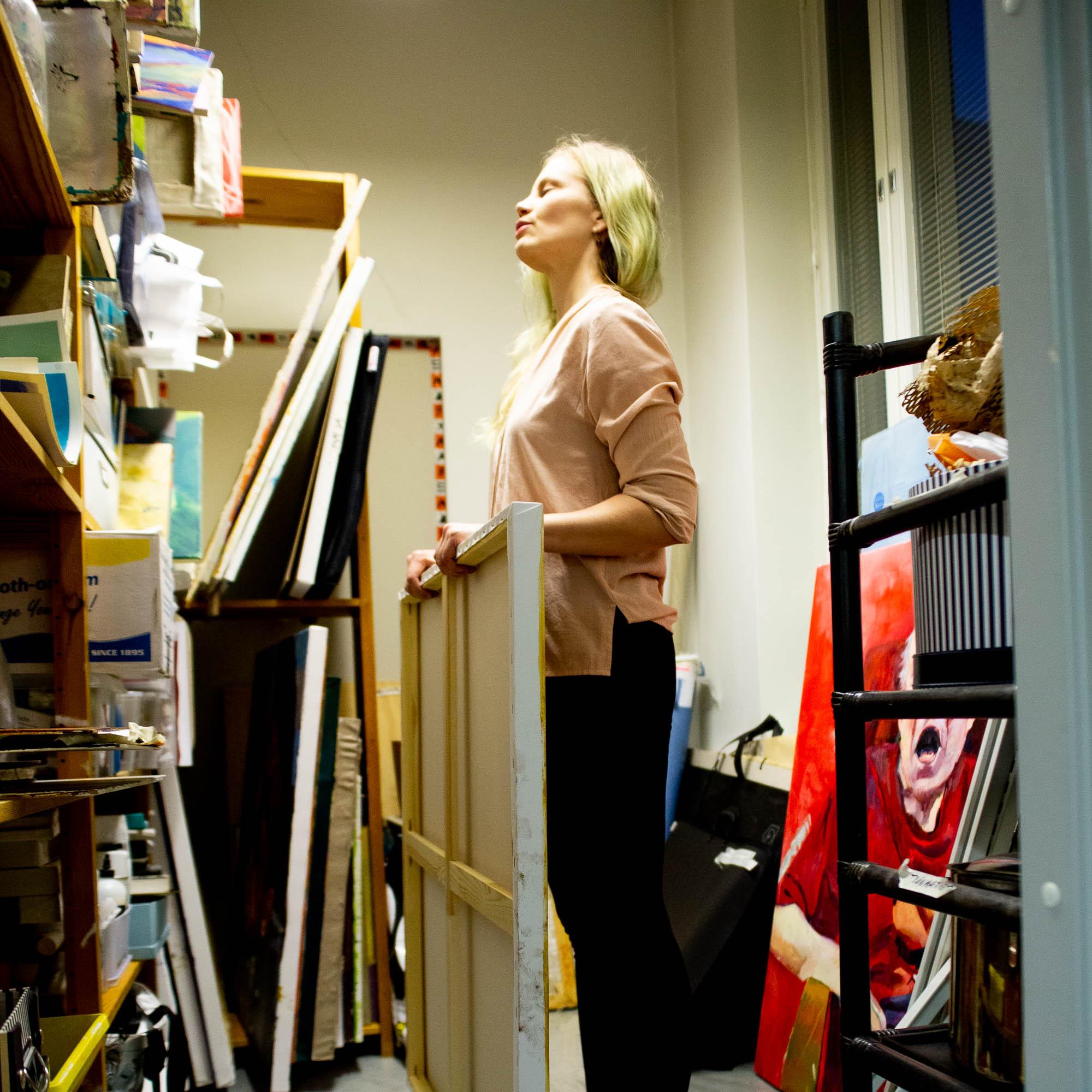 Nainen maalaus käsissään, seisoo katse ylöspäin pienessä kirkkaasti valaistussa varastohuoneessa
