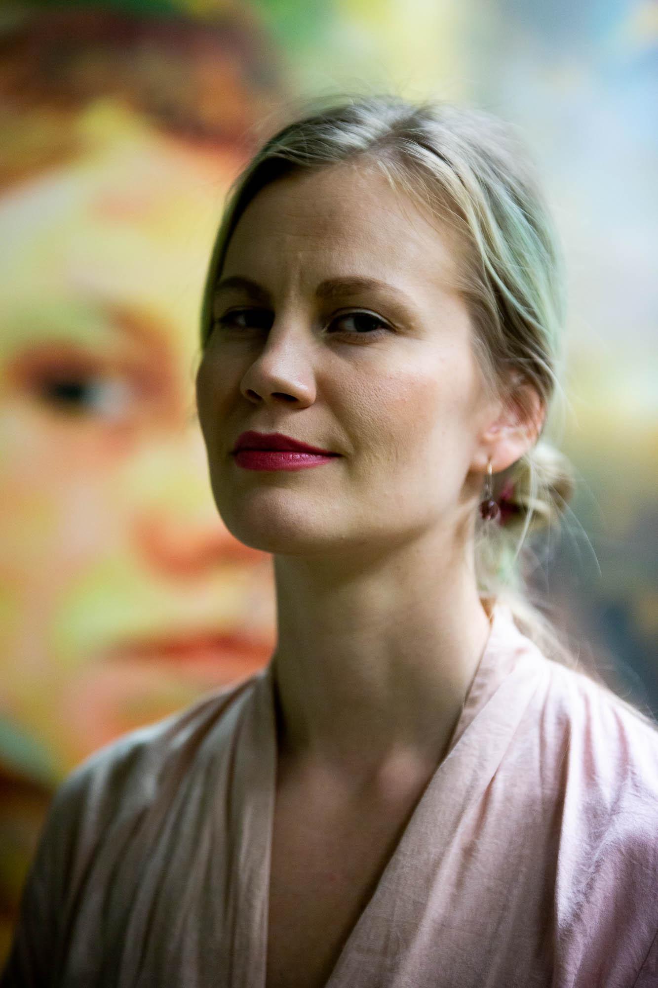 Muotokuva nuorehkosta naisesta, sivuprofiili, katse kameraan, taustalla epätarkka maalaus