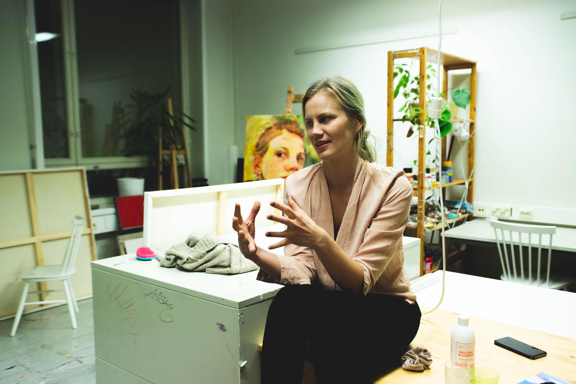 Nainen istuu pöydällä ja selittää käsillään, taustalla taidetarvikkeita avarassa huoneessa.