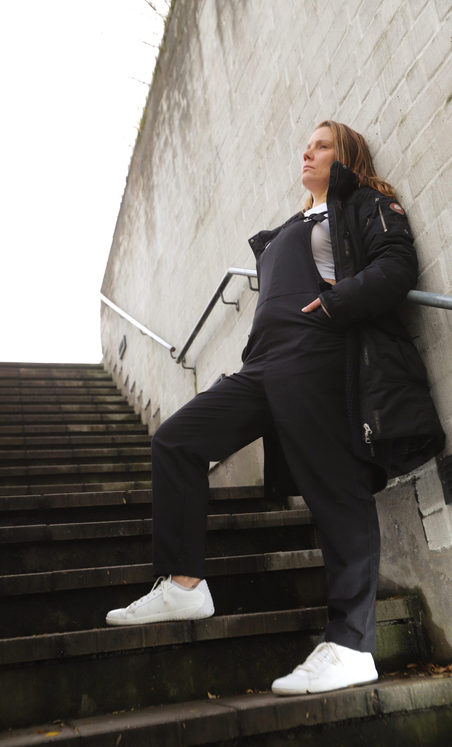 Nainen nojaamassa ulkona portaikossa seinää vasten