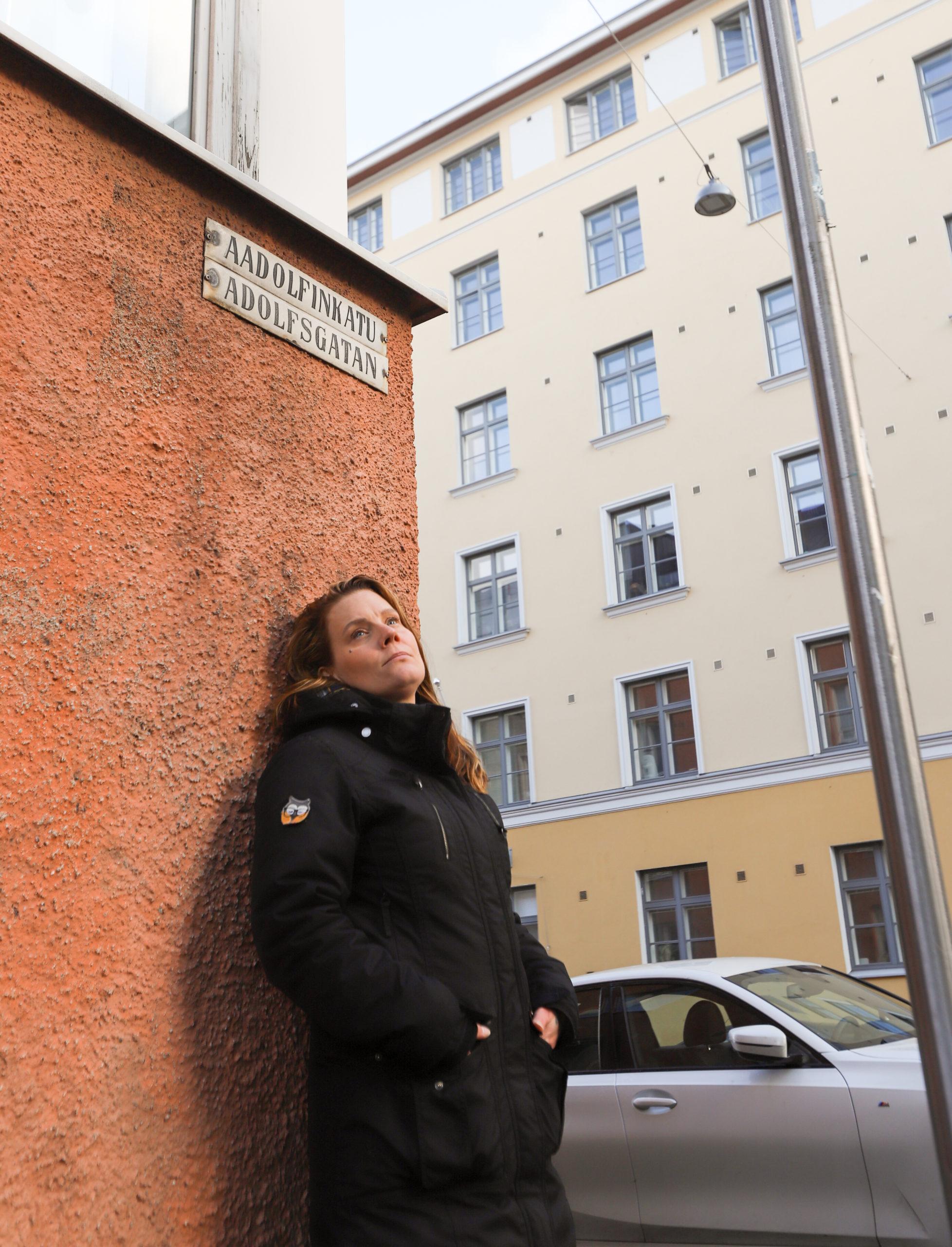 Nainen nojaamassa kadunkulmaan, taustalla näkyy kadunkyltti ja kerrostalo