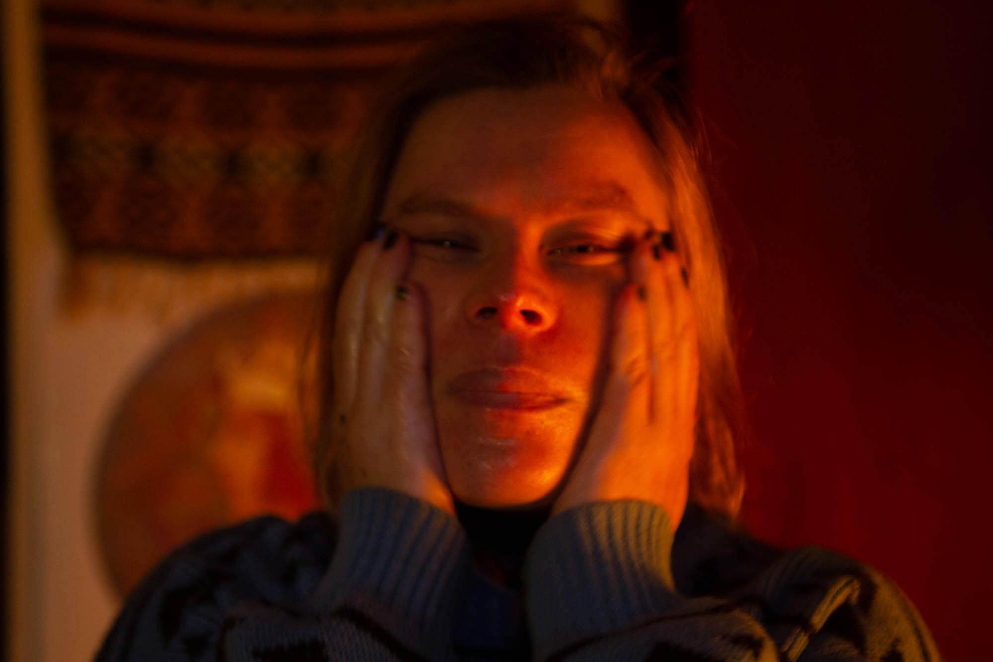 nainen levittää voidetta kasvoilleen kynttilänvalossa