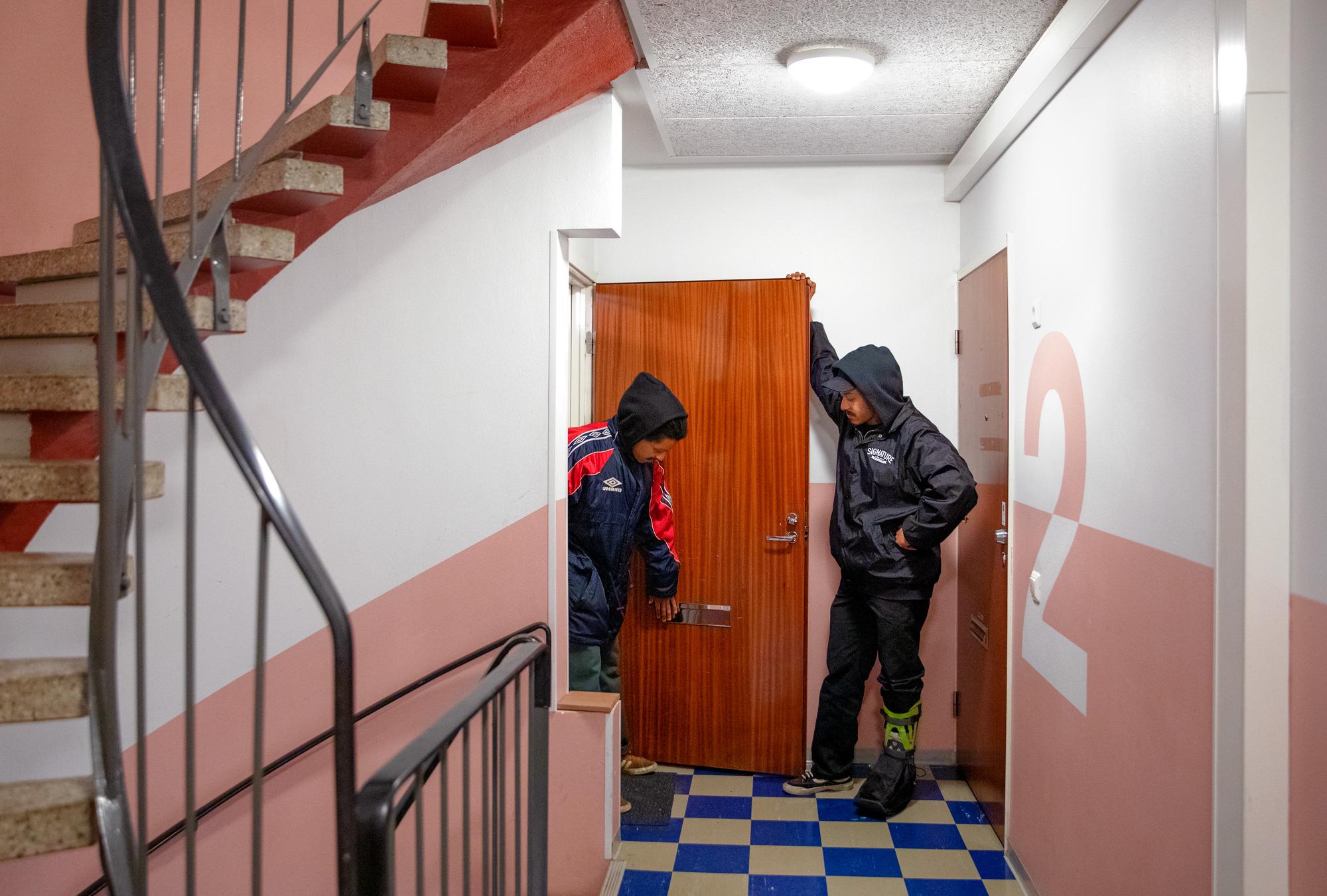 Kaksi miestä seisoo oviaukossa kerrostalon käytävässä.