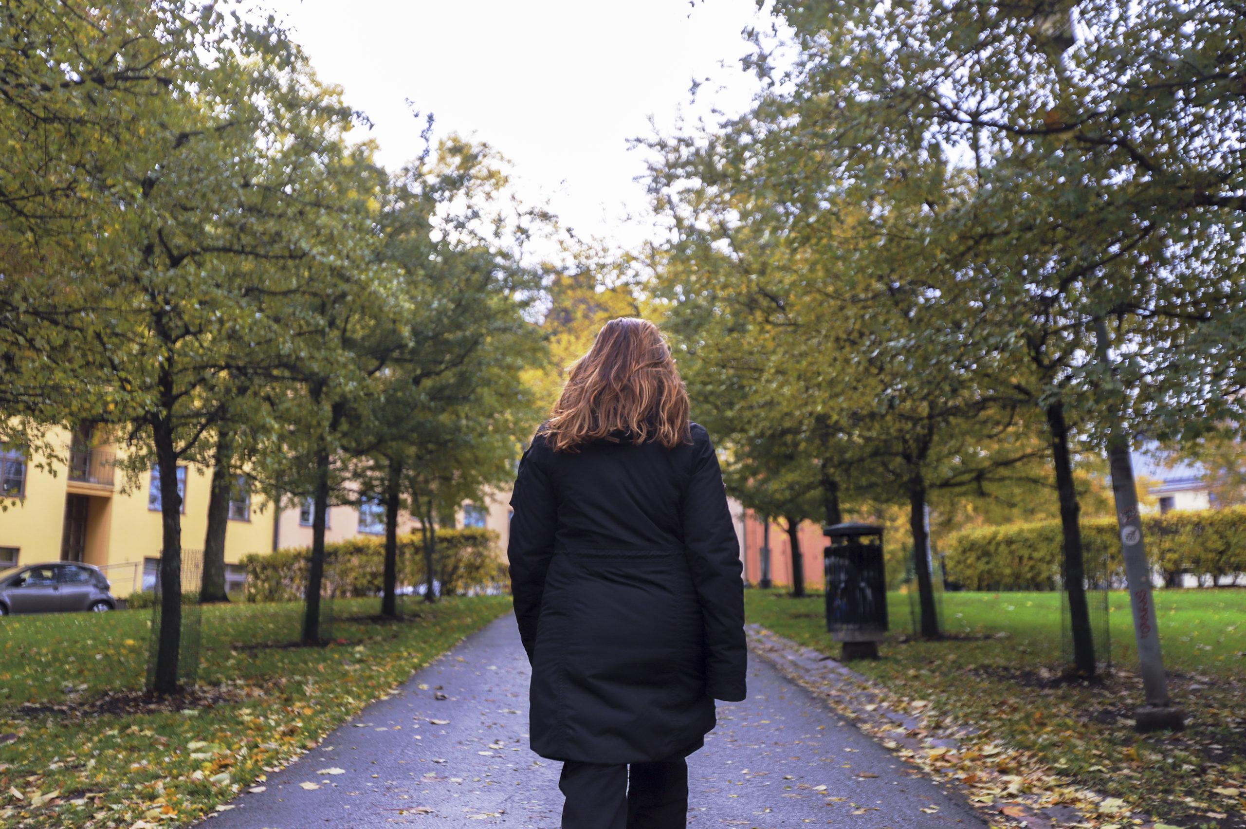 Nainen kävelemässä katua pitkin selin kameraan