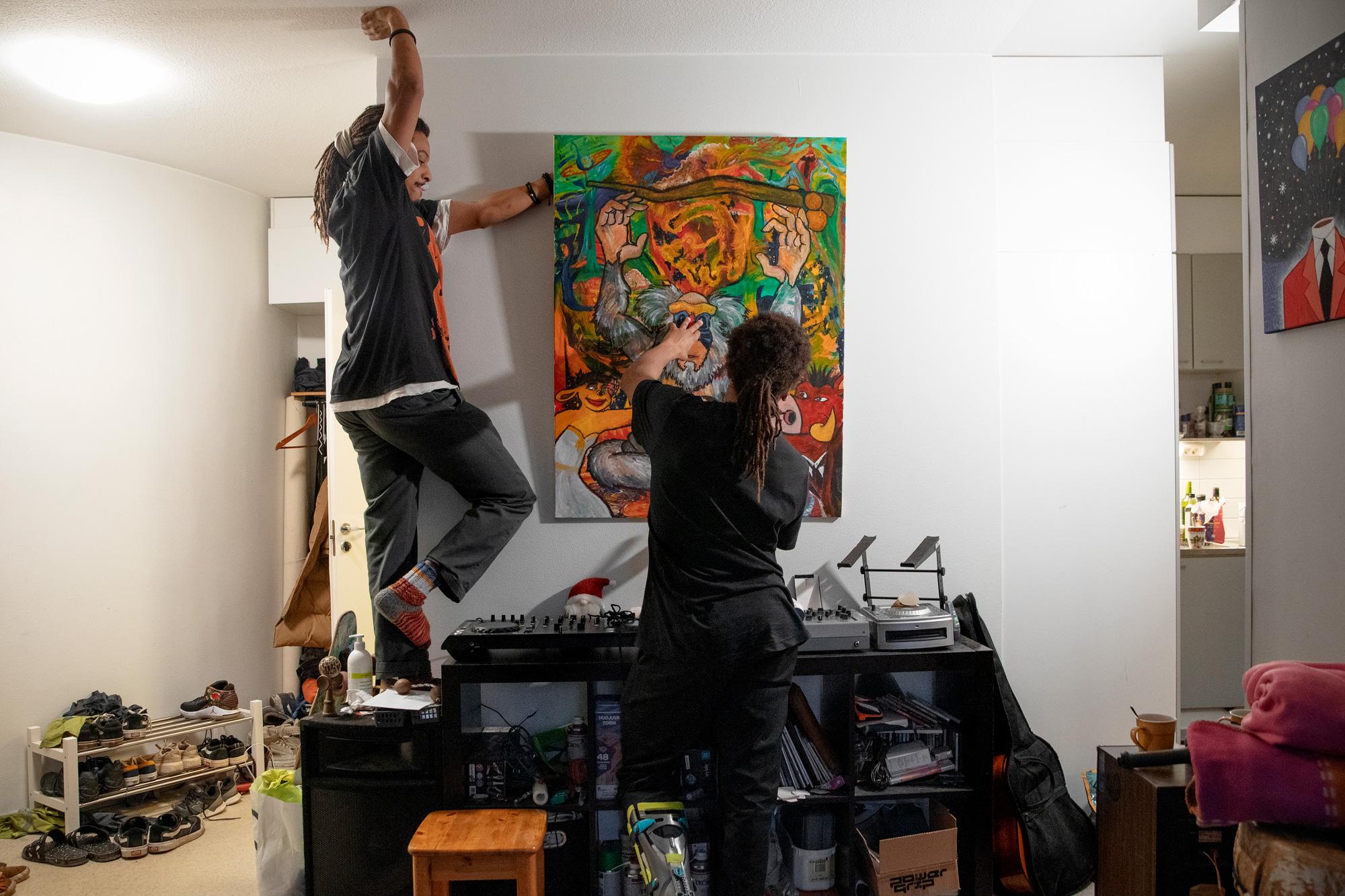 Kaksi miestä laittaa taulua seinälle.