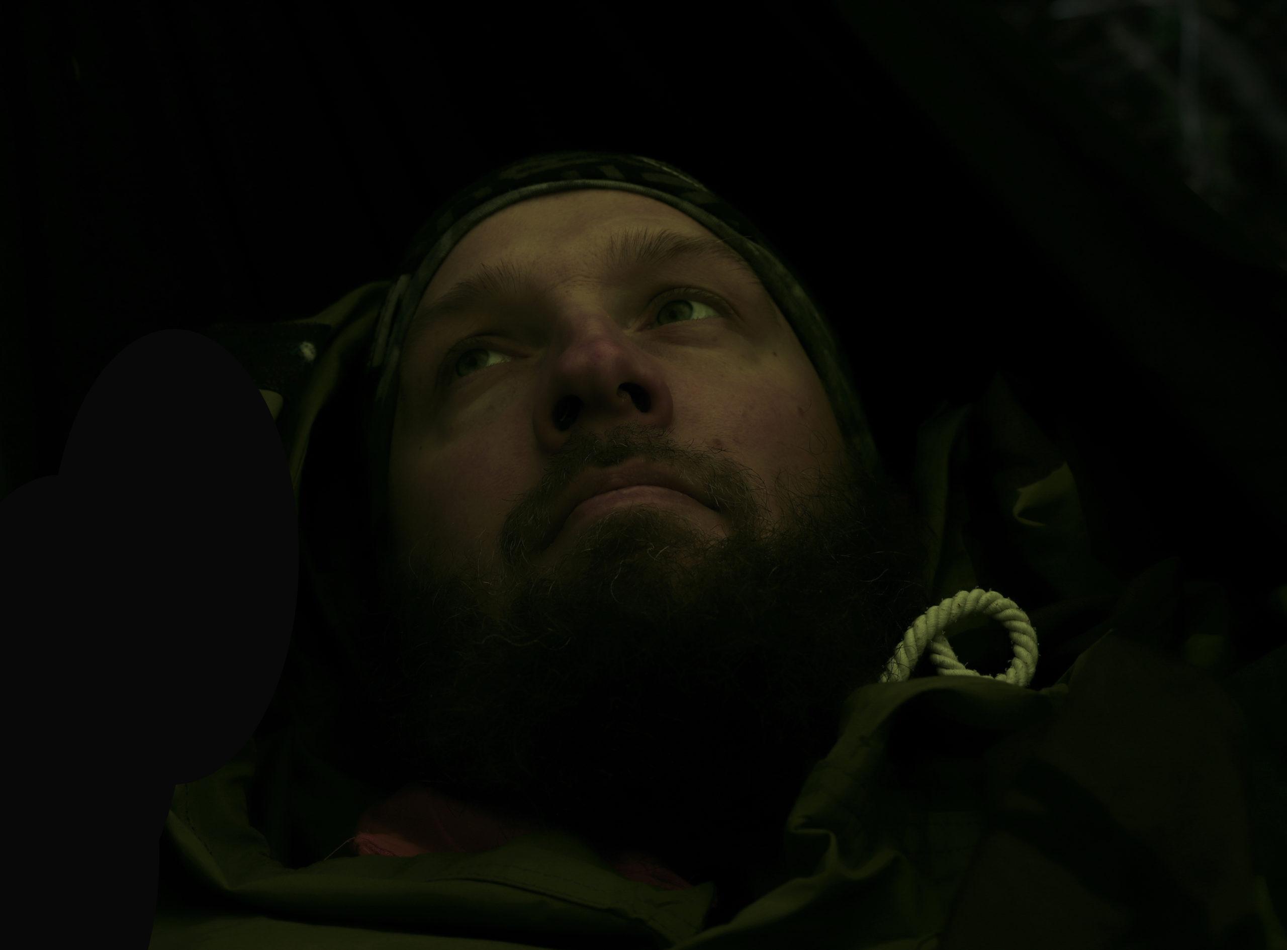 Miehen kasvot pimeää taustaa vasten