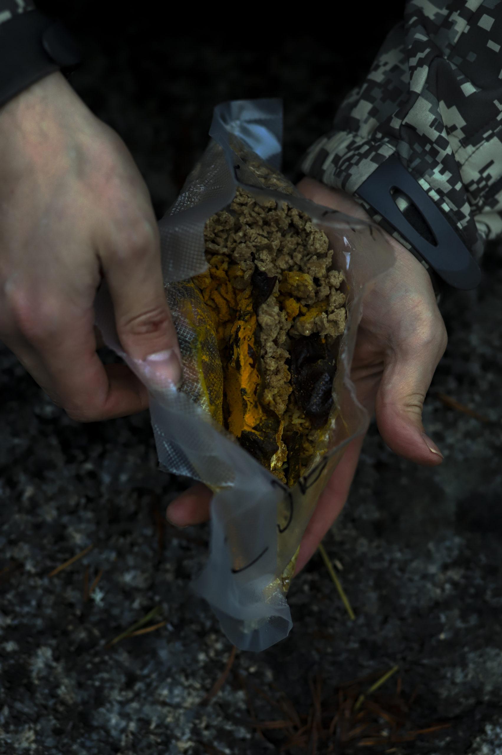 Lähikuva käsistä, jotka pitelevät kuivaruokaa muovitaskussa