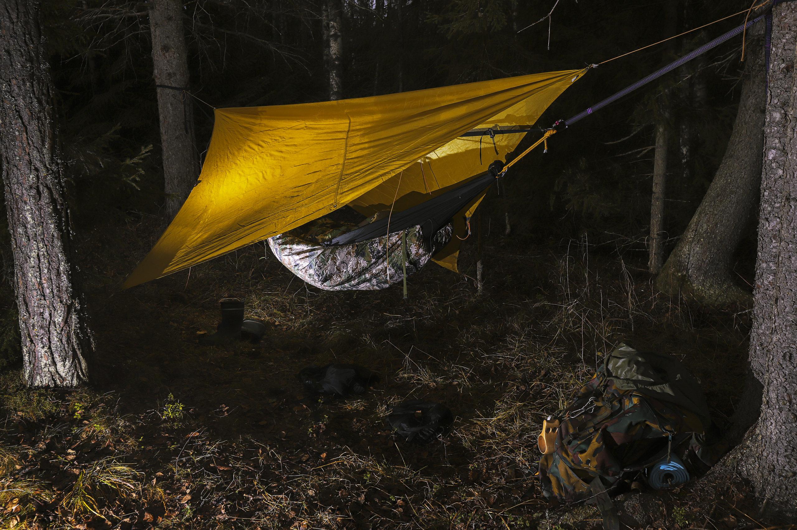 Pimeää taustaa vasten näkyy riippumatto metsässä, jonka yllä keltainen kangas