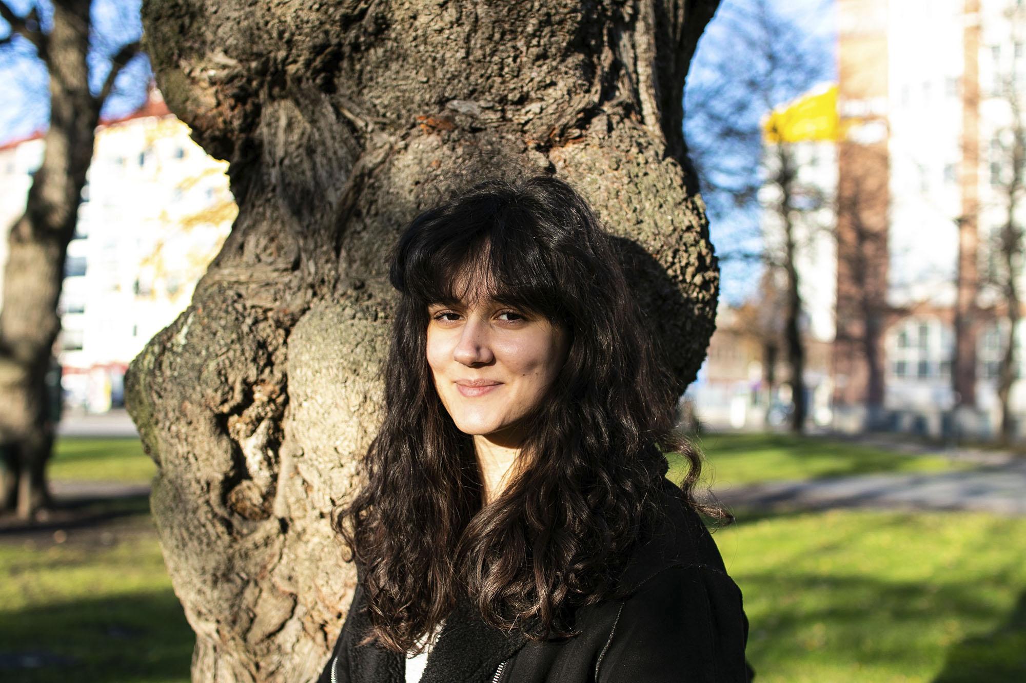 Henkilökuva naisesta ulkona puun edessä aurinkoisessa säässä.