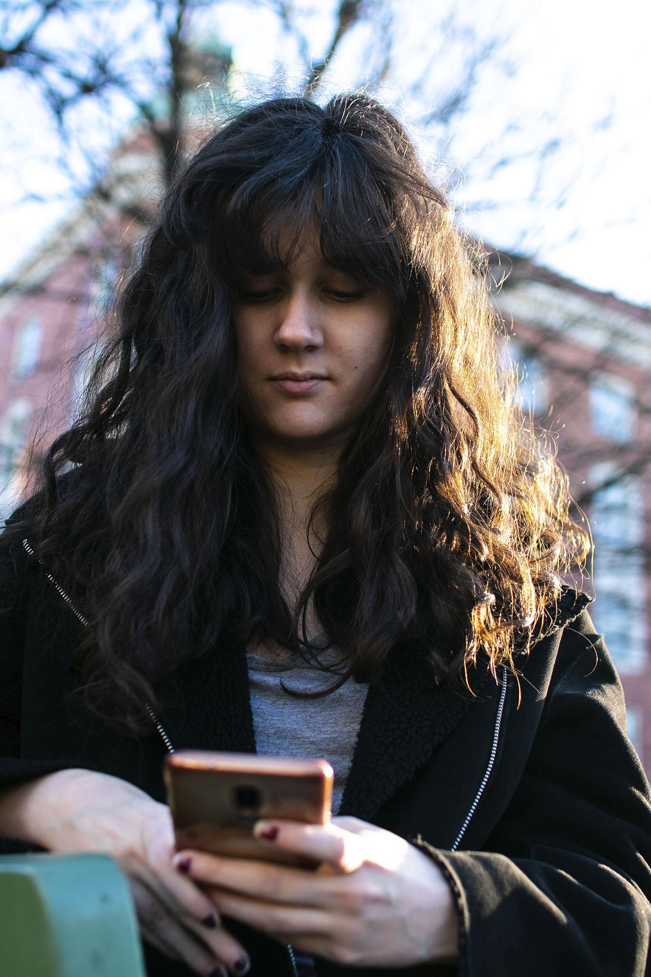 Nainen katsoo kännykkää.