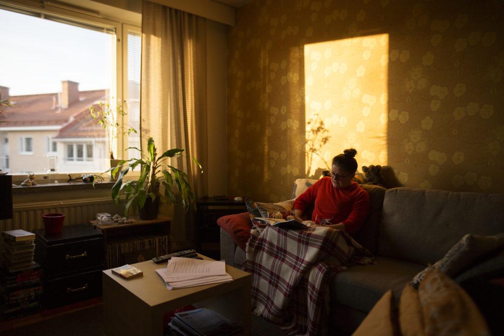 Kuvassa henkilö istuu sohvalla auringonpaisteessa.