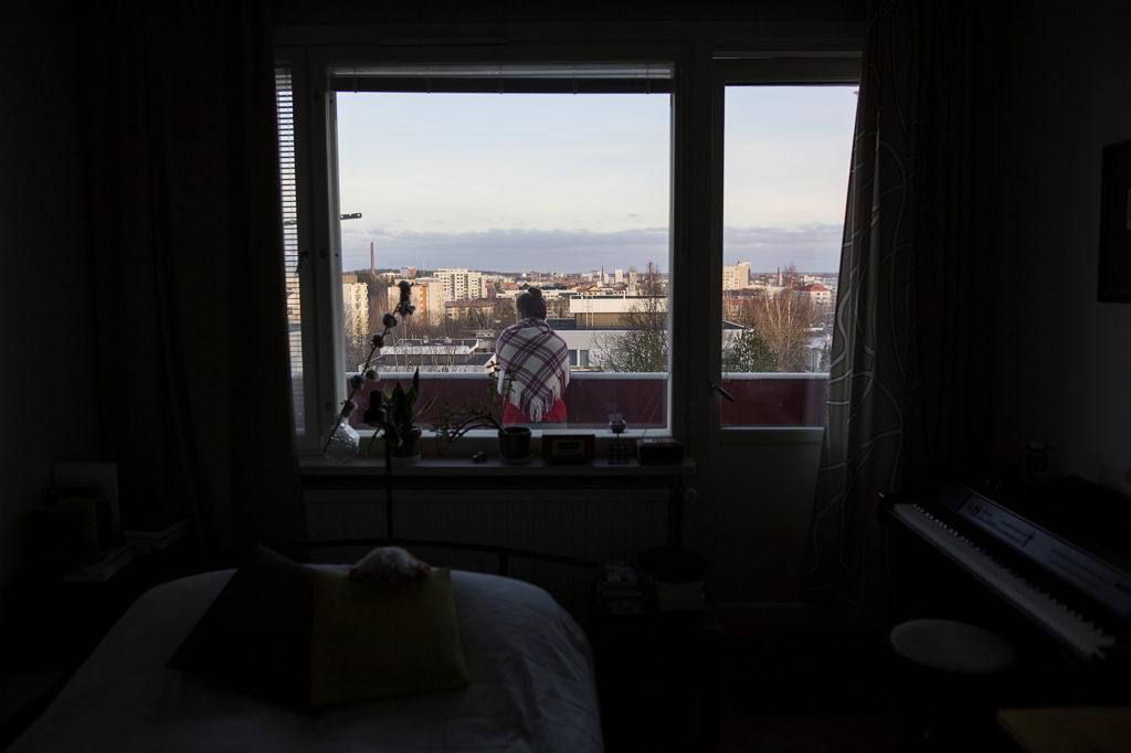 Kuvassa henkilö parvekkeella ja taustalla kaupunki.