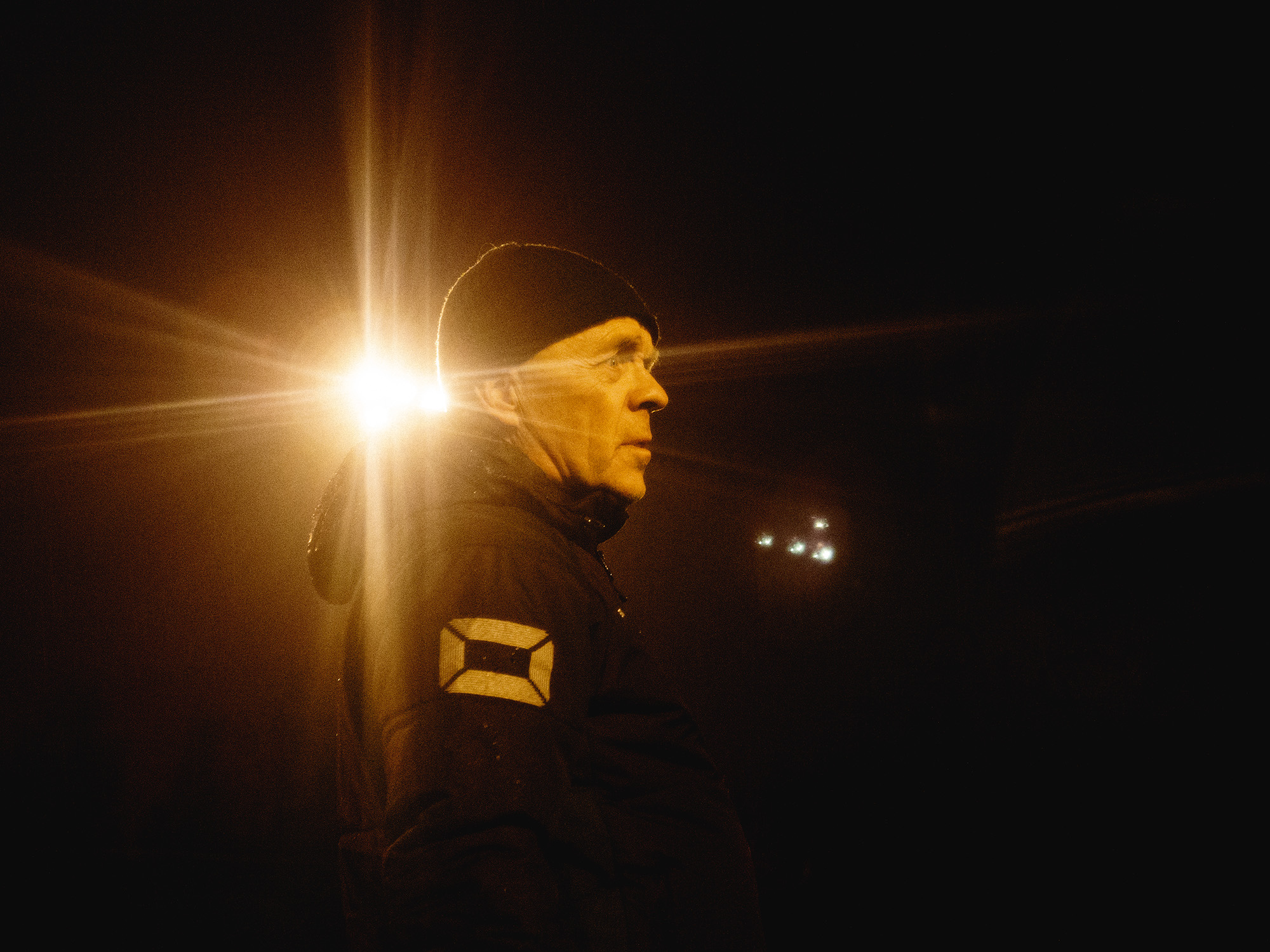 Miehen sivuprofiili, takana kirkas valo.