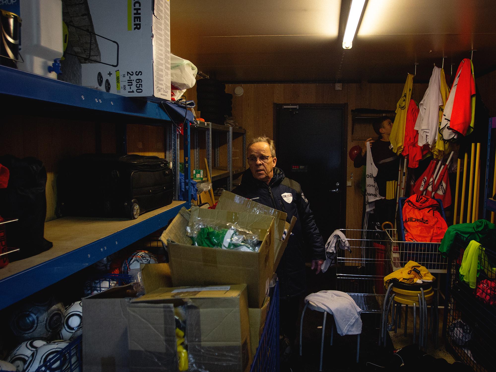 Mies seisoo varaston sisätilassa. Taustalla nuorempi mieshenkilö kurottaa hyllylle.