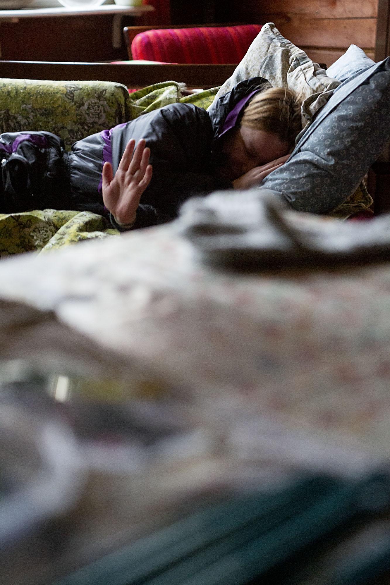 nainen makaa toppahaalareissa vanhalla sohvalla, heilauttaa kättään nauraen tyynyyn