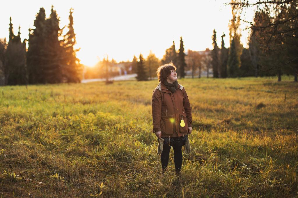 Kuvassa henkilö seisomassa auringonlaskussa nurmialueella.