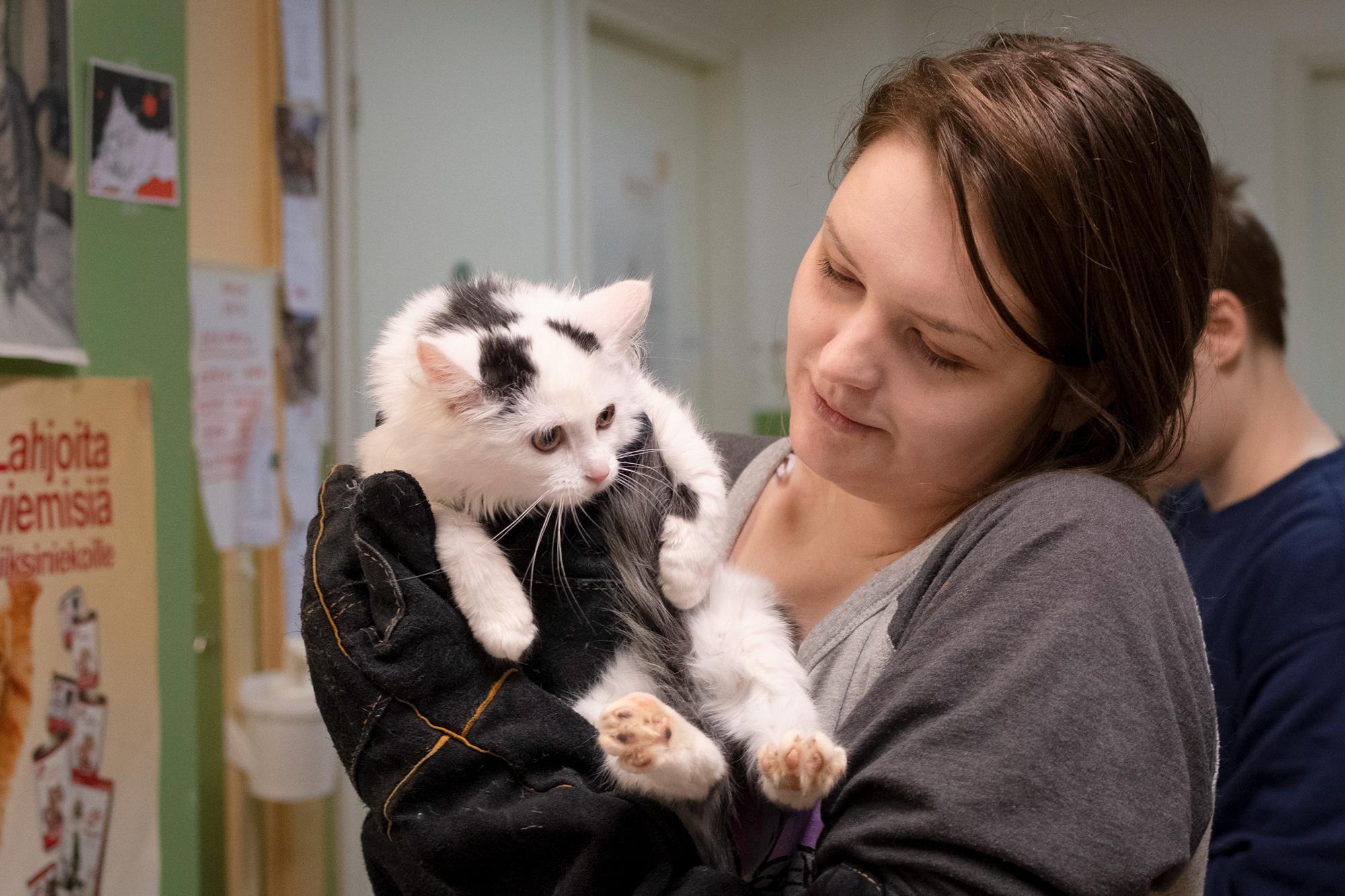 Nainen pitää kissaa sylissä ja katsoo kissaa.