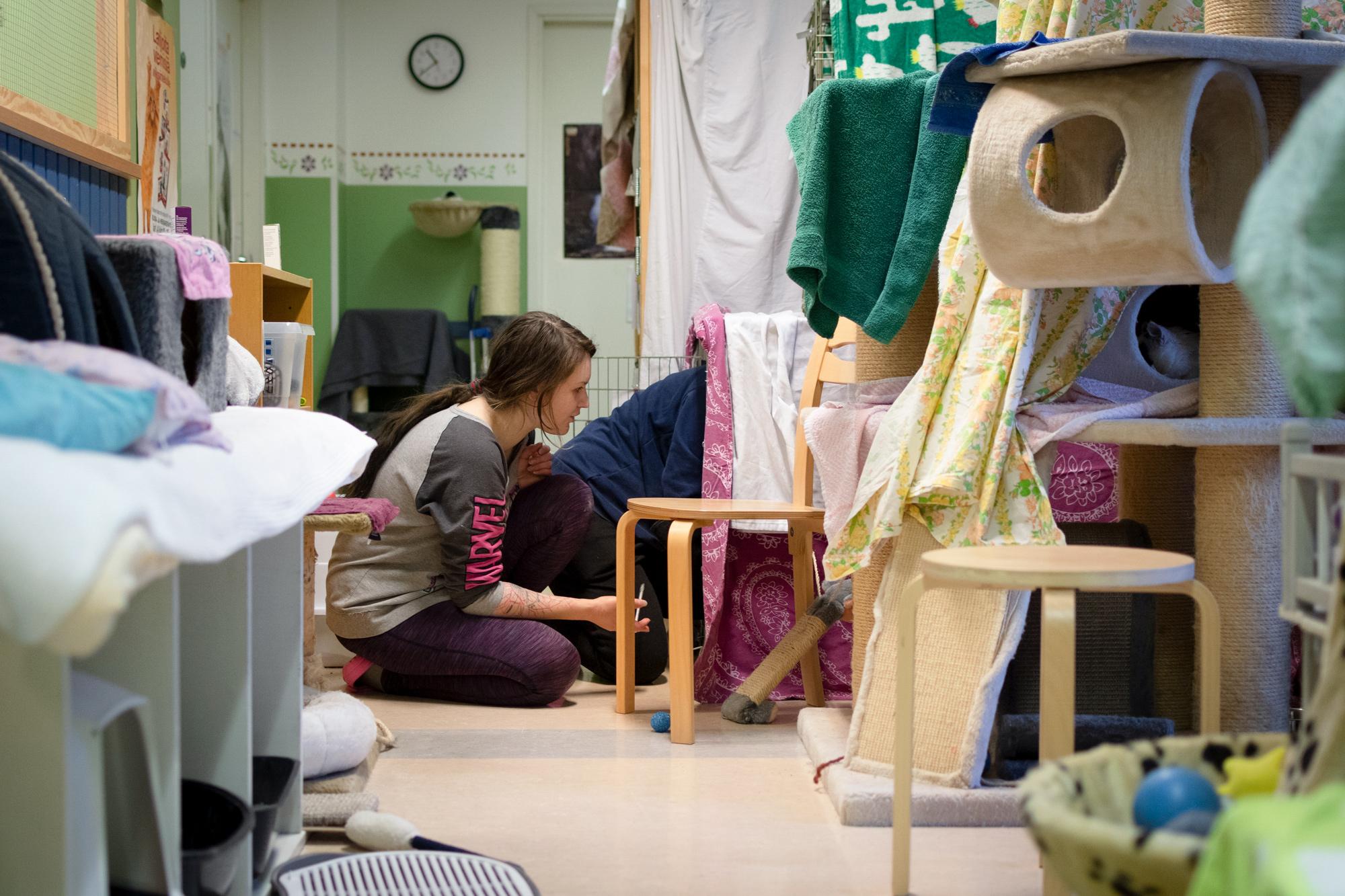 Nainen istuu huoneen lattialla.