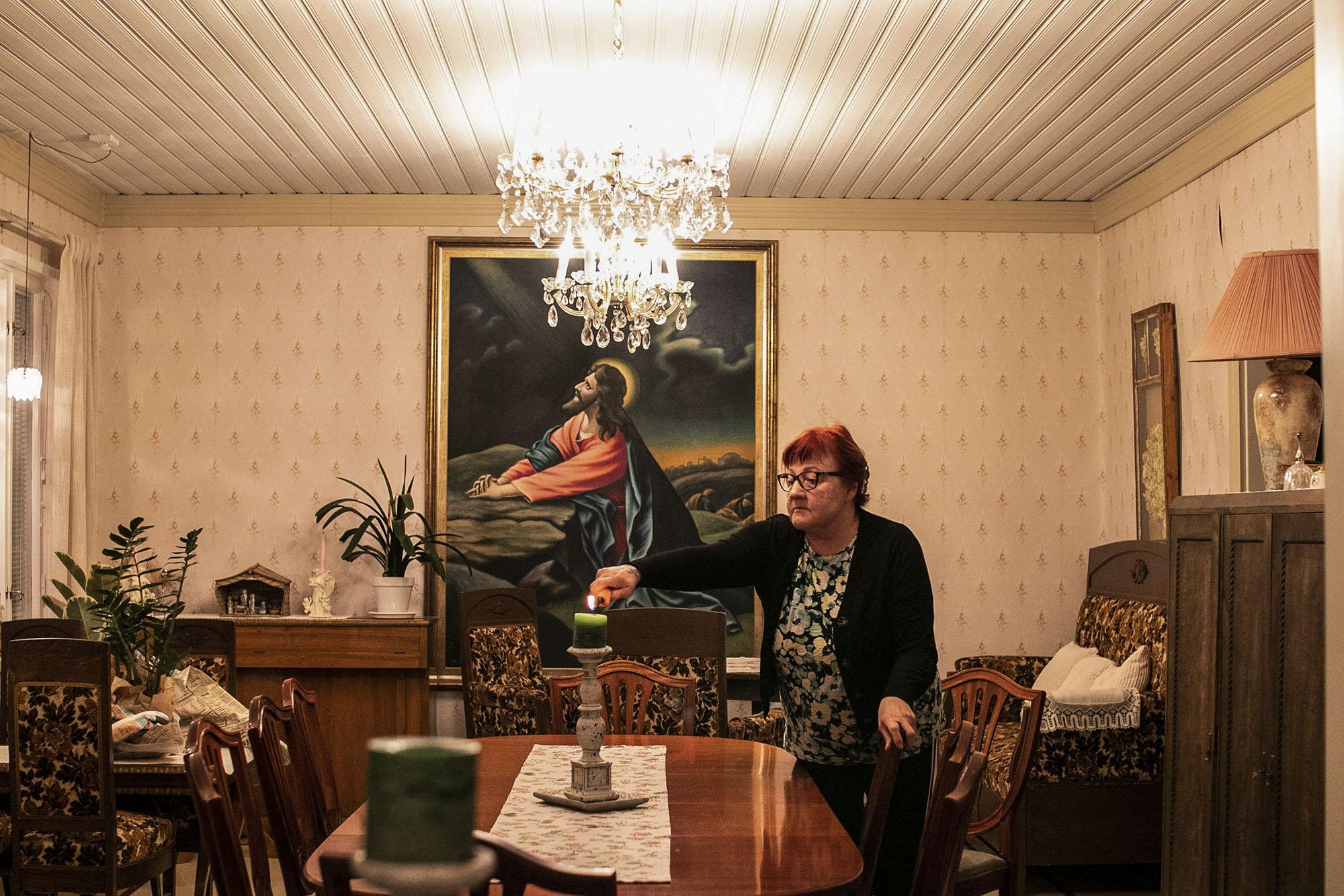 Nainen sytyttää kynttilän palamaan sisätilassa.