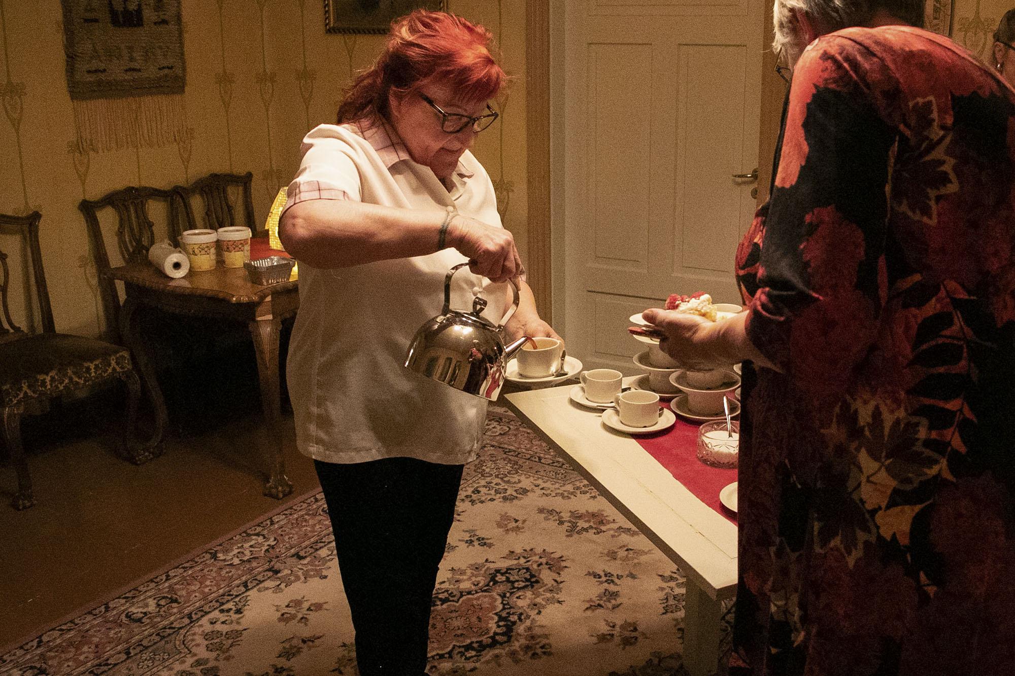 Nainen kaataa kahvia kuppiin.
