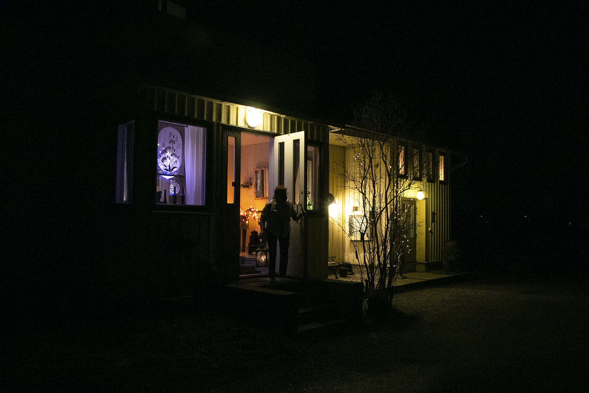 Ulkokuva talosta, jouluvaloista ja naisesta pimeässä.