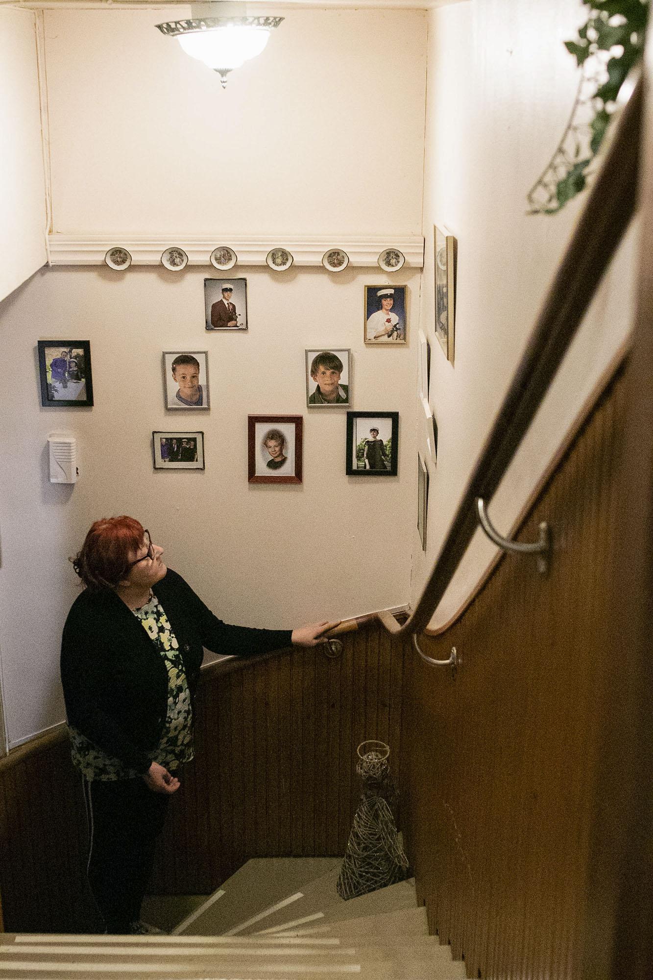 Nainen katsoo valokuvia portaissa.