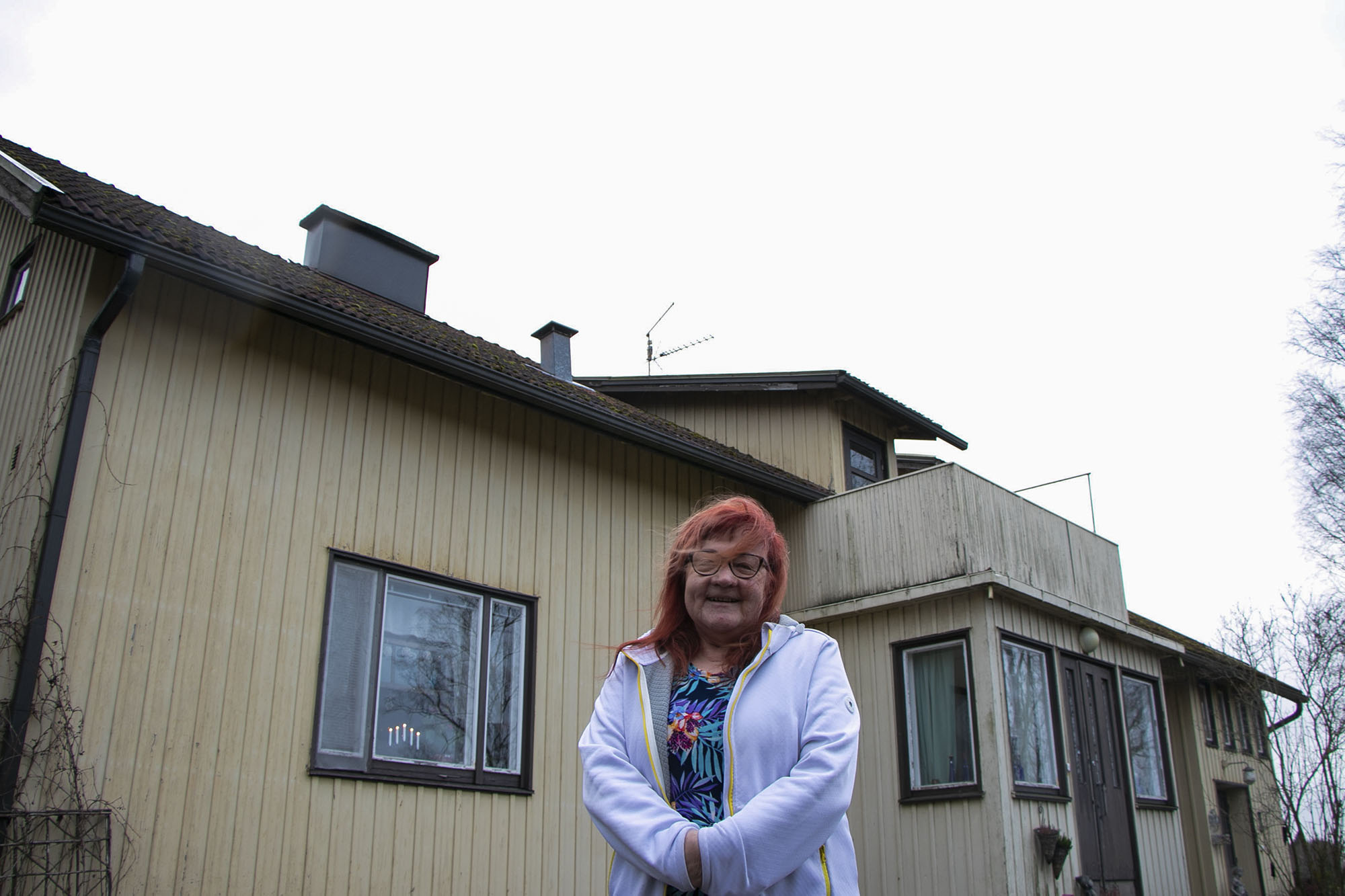 Nainen ulkona talon edessä.